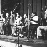 """Απ'τ'αριστερά: Νίκος Λογοθέτης, Στέλιος Χρυσίνης, Μπαγιαντέρας, Π.Μιχαλόπουλος, Ρούλα Νοικοκυράκη, Σπύρος Καλφόπουλος, Στ.Κηρομύτης, Μιχάλης Γενίτσαρης, Ιορδάνης και Νίκος Περγιάλης (με γυρισμένες τις πλάτες του). (""""Ρουαγιάλ"""", 25.8.1975)."""