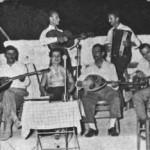 Ορθιος με την κιθάρα ο Γιάννης Σταμούλης ή Μπιρ Αλάχ. Καθιστοί απ'τα αριστερά: Απόστολος Χατζηχρήστος, Λ.Γουναρόπουλος και Μήτσος Μπατάγιας (με την κιθάρα). Πειραιάς 1945.