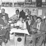 Πρώτος δεξιά ο Κλουβάτος και πίσω του ο Μάρκος Βαμβακάρης. Αριστερά ο Κ.Ρούκουνας (στο βάθος) και ο Ρουμελιώτης με το μπουζούκι. Η τραγουδίστρια είναι η Καίτη Γκραίη.