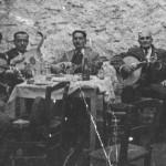 Γ.Πατίδης (βιολί), Μήτσος Τζόρας (κλαρίνο), Τάσος Κόνιαλης (λαούτο), Αγγελος; (ούτι), Ευγένιος; (κανονάκι). Στο κέντρο με το μπουζούκι ο Κοσμάς Κοσμαδόπουλος. Χωρίς πάλκο, χωρίς μικρόφωνα (Ν.Ιωνία, 1934).