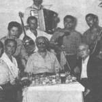 Από τ'αριστερά Γιάννης Μπαφούνης ή Σαμιώτης, Θόδωρος Πολυκανδριώτης, Μπέμπα Μπλανς, Μπέμπης Στεργίου, ο τούρκος Ρομπέν (ούτι) και ο περίφημος κατασκευαστής οργάνων Τσακιριάν. Στου Κεφάλα.